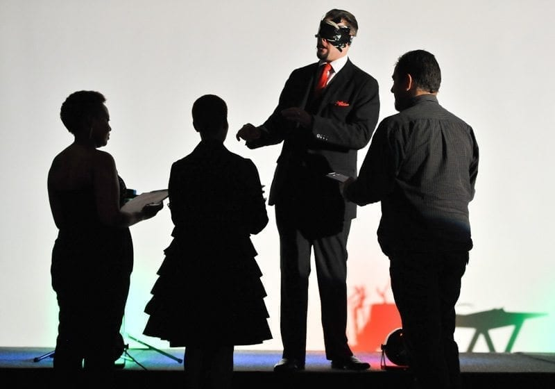 Audience members interact with magician Marcel Oudejans on stage