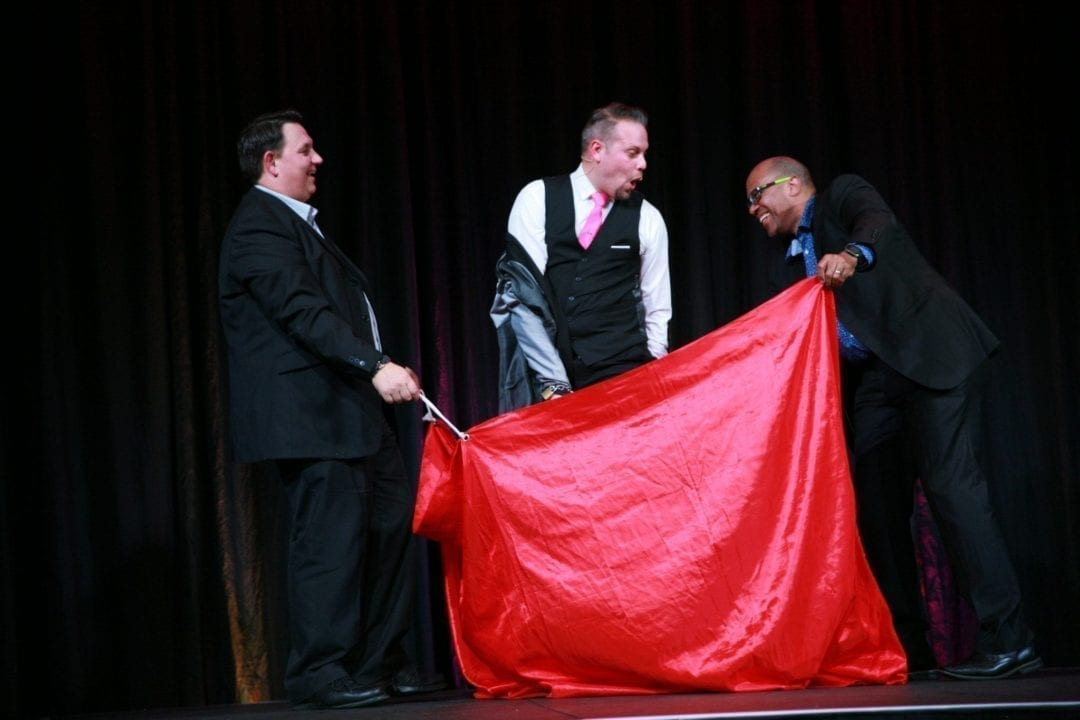 Volunteers on stage laughing as they are assisting magician Marcel Oudejans